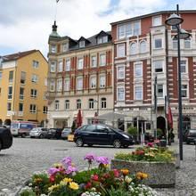 Johannisplatz mit Blumen, Autos und Jugendlichen