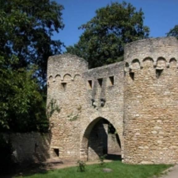 """© Copyright/Quelle: www.ingelheim.de • Die Wehrmauer in Ober-Ingelheim wurde vermutlich im frühen 15. Jahrhundert errichtet. Sie besitzt einen Zinnenkranz und ist bis zu 8 m hoch und bis zu 2 m dick. Über eine längere Strecke war der Mauer ein Graben mit Bachlauf vorgelagert. Das von der Wehrmauer eingeschlossene Gelände hätte den Einwohnern im Falle eines Angriffs zum Rückzug dienen sollen, was aber nie nötig war. In die Mauer waren mehrere Türme eingefügt, die zum Teil noch erhalten und an ihren charakteristischen Steinkegeldächern zu erkennen sind. Ebenfalls noch erhalten sind das """"Uffhubtor"""" und das Ohrenbrücker Tor. • © Copyright/Quelle: www.ingelheim.de"""